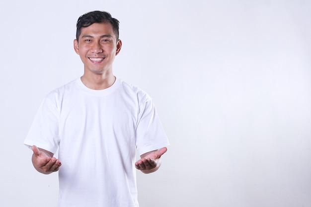 Een aziatische volwassen man die een wit t-shirt draagt en zijn handen laat zien met een lachend gezicht