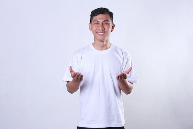 Een aziatische volwassen man die een witte tshir draagt en zijn armen voor zijn borst opent met een glimlach