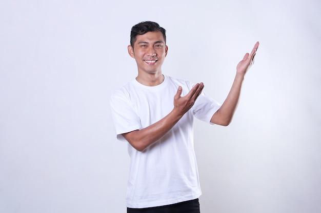 Een aziatische volwassen man met een wit t-shirt kijkt vooruit en opent zijn armen opzij