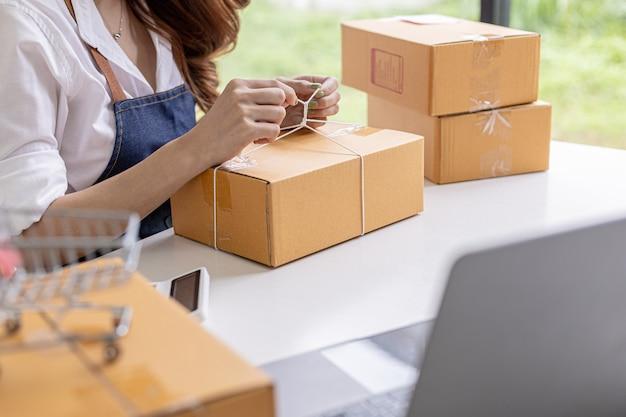 Een aziatische vrouw bindt een pakket aan de doos van een klant, ze heeft een online winkel, ze verpakt en verzendt via een particulier transportbedrijf. online verkoop en online winkelconcepten.