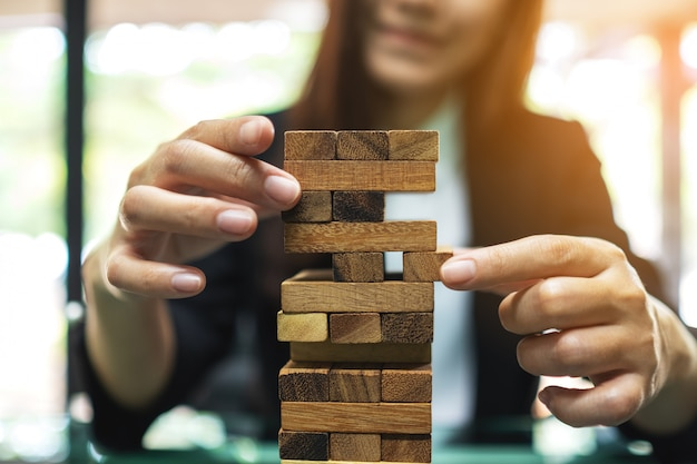 Een aziatische vrouw bouwt tumble-toren houten blokken voor beheer en strategie in bedrijfsconcepten