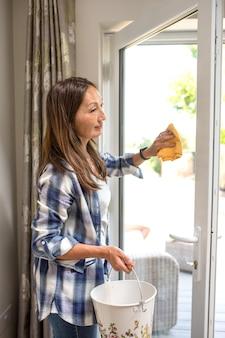Een aziatische vrouw die blauw overhemd schoonmakend venster in een ruimte draagt