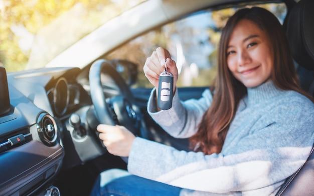 Een aziatische vrouw die de autosleutel vasthoudt terwijl ze in de auto zit