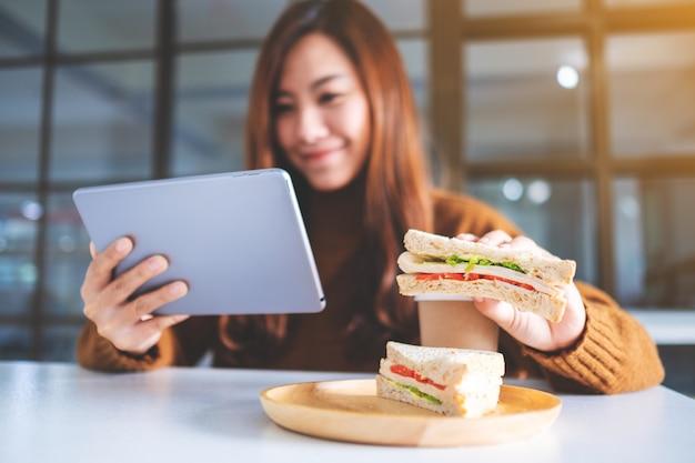 Een aziatische vrouw die een volkoren sandwich vasthoudt en eet terwijl ze een tablet-pc gebruikt