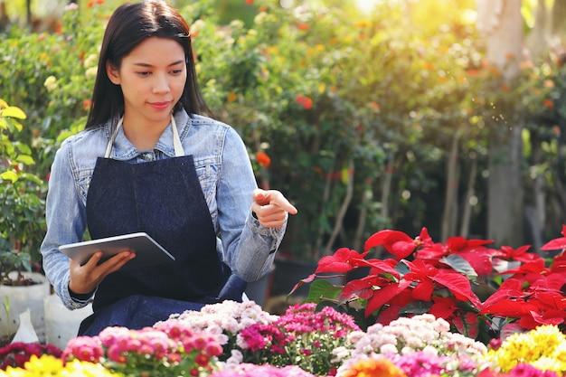 Een aziatische vrouw die eigenaar is van een bloementuinbedrijf, telt de bloemen in overeenstemming met de bestelling van de klant.