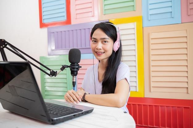 Een aziatische vrouw die lacht terwijl ze een koptelefoon draagt en een laptop voor een microfoon gebruikt