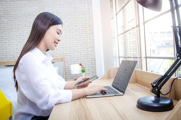 Een aziatische vrouw die thuis zit houd de smartphone vast en typ de informatie op de laptop