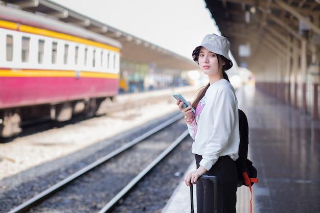 Een aziatische vrouw draagt een tas en een smartphone op zoek naar reisinformatie