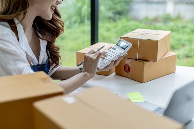 Een aziatische vrouw drukt op een witte rekenmachine, ze heeft een online winkel, ze gebruikt een bestelbedragcalculator om een overzicht te krijgen van het bedrag dat klanten moeten betalen. online verkoopconcept.