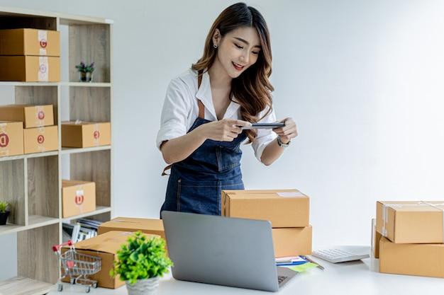 Een aziatische vrouw gebruikt een smartphone om foto's te maken voor een pakketdoos als bewijsmateriaal, ze heeft een online winkel, ze verpakt en verzendt via een particuliere rederij. online verkoopconcept.