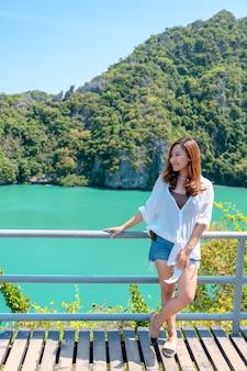 Een aziatische vrouw stond aan de blauwe zee op het prachtige landschapseiland