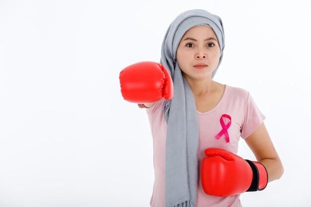 Een aziatische vrouw ziekte borstkanker patiënt gevechten tonen bokshandschoenen borstkanker bewustzijn maand geïsoleerd op witte lege kopie ruimte studio achtergrond, gezondheidszorg, geneeskunde concept