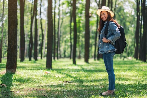 Een aziatische vrouwelijke reiziger met een hoed en rugzak op zoek naar een prachtige dennenbossen