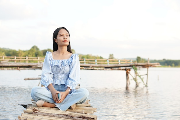 Een aziatische vrouwelijke toerist zit op een bamboebrug om het uitkijkpunt te bereiken