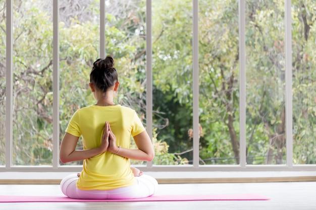 Een aziatische vrouwelijke yogaleraar die een geel shirt draagt, traint haar lichaam om sterk en gezond te zijn met yoga.