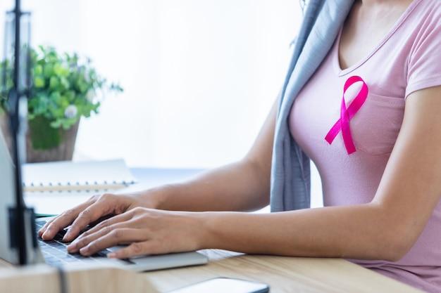 Een aziatische vrouwenziekte borstkankerpatiënt met roze lint die hoofddoek draagt na behandeling voor chemotherapie met werkende zaken op laptop in kantoor thuis, geneeskundeconcept