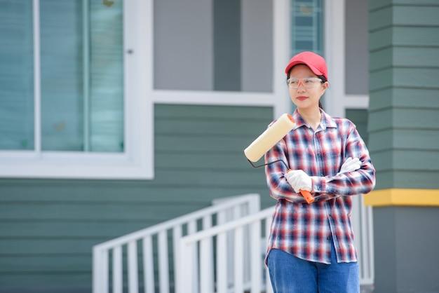Een aziatische werkneemster die huisschilder is sta vol vertrouwen je verfrollerborstel vast.