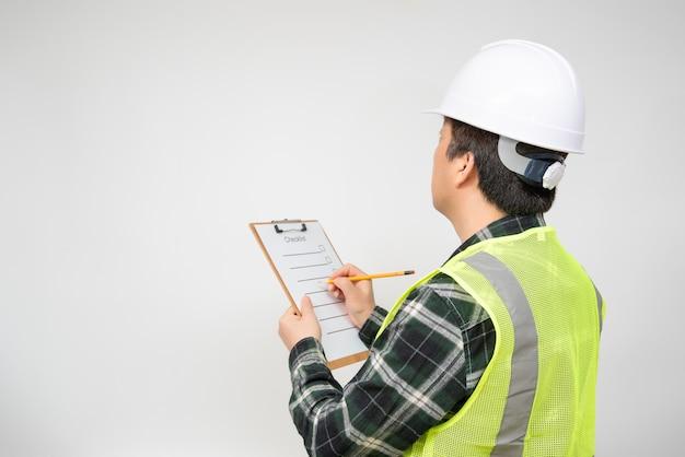 Een aziatische werknemer op middelbare leeftijd die iets controleert met een controlelijst in zijn hand.