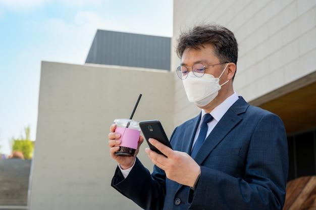 Een aziatische zakenman van middelbare leeftijd in de stad die een masker draagt, een koffiekopje vasthoudt en een smartphone gebruikt.