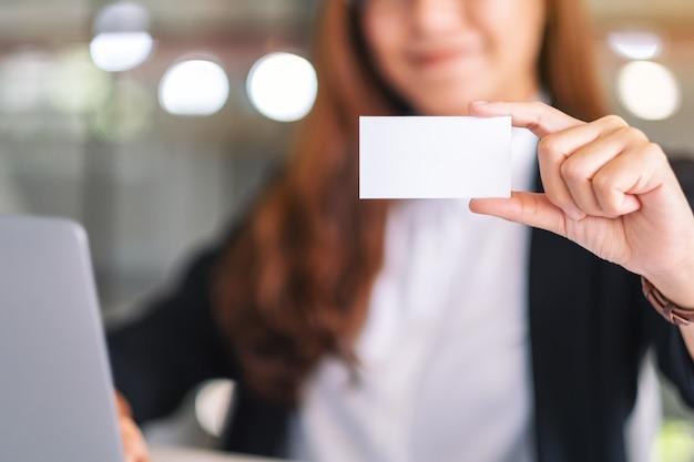 Een aziatische zakenvrouw die een blanco visitekaartje vasthoudt en toont tijdens het gebruik van een laptopcomputer op kantoor