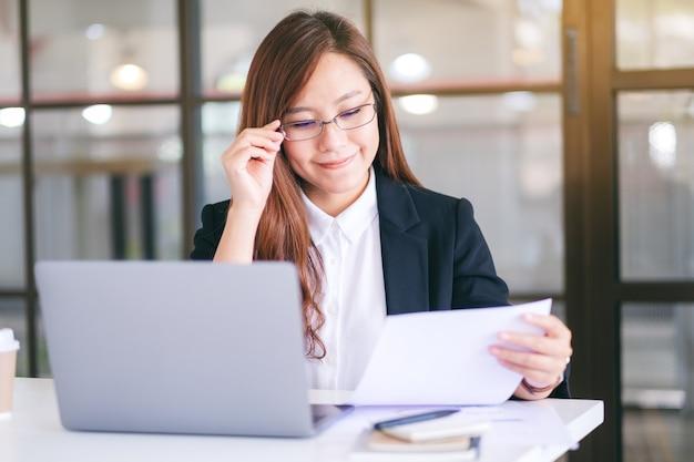 Een aziatische zakenvrouw die een laptopcomputer en papierwerk op kantoor gebruikt en eraan werkt