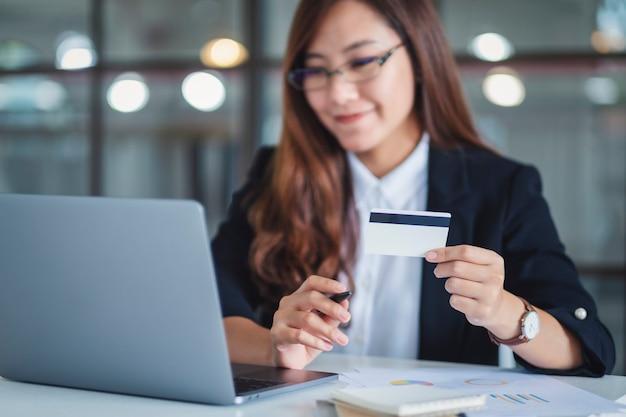 Een aziatische zakenvrouw met creditcards tijdens het gebruik van een laptopcomputer op kantoor