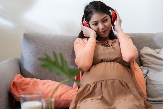 Een aziatische zwangere vrouw glimlacht en zit op de bank en luistert naar muziek met een gelukkig en ontspannen gevoel.