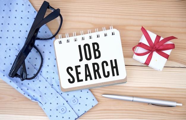 Een baan nodig, op zoek naar. tekst in handen op wit bureau van boven naar beneden