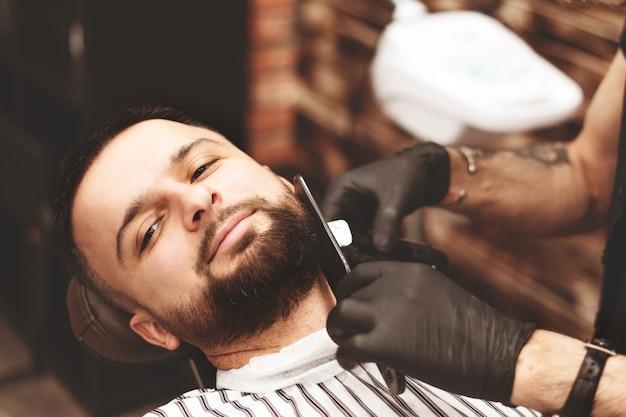 Een baard scheren in een kapperszaak met een gevaarlijk scheermes. kapper winkel baardverzorging. drogen, knippen, een baard knippen. selectieve aandacht.
