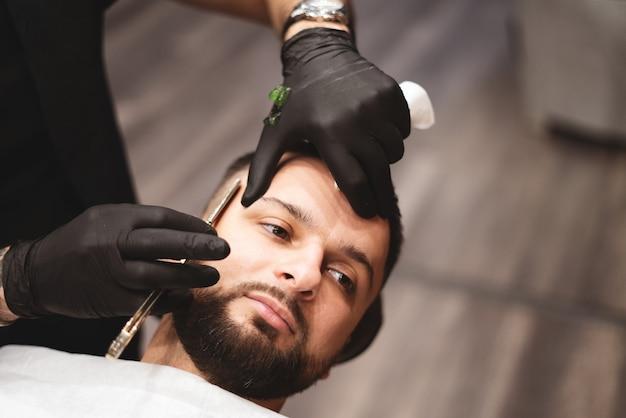 Een baard scheren in een kapperszaak met een gevaarlijk scheermes.