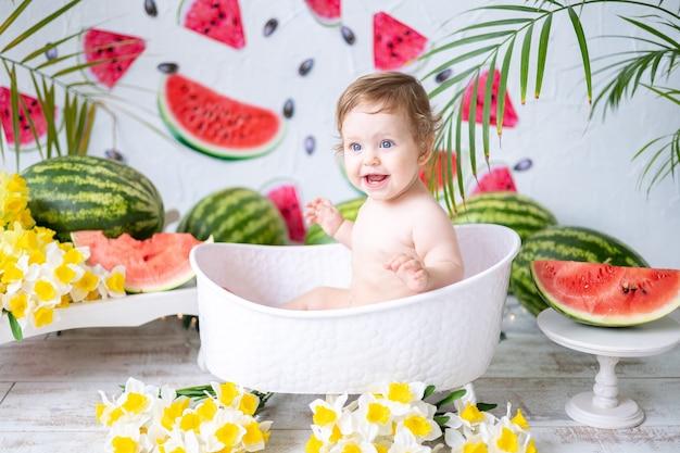 Een baby een meisje een close-upportret tegen een achtergrond van watermeloenen die lachen en zich verheugen