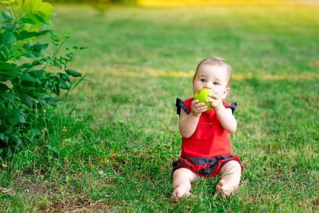 Een baby eet een groene appel in een rode bodysuit op het groene gras in de zomer, ruimte voor tekst