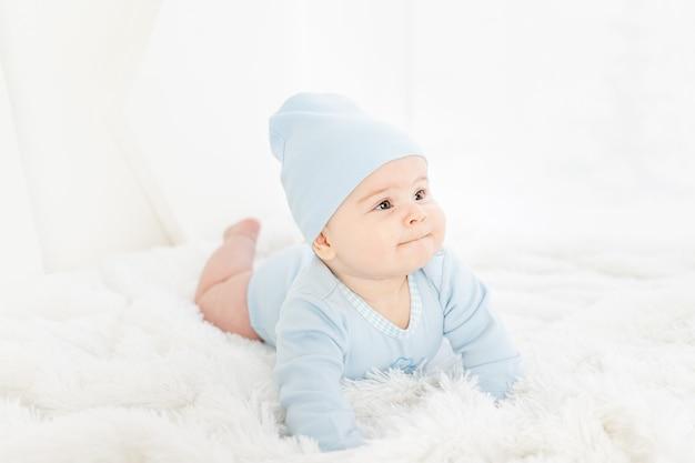 Een baby in blauwe kleren ligt op zijn buik op een wit tapijt