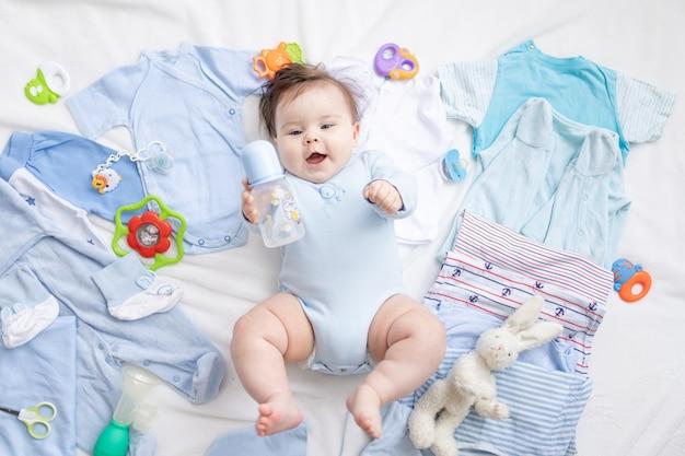 Een baby in blauwe kleren ligt tussen de accessoires en kleding van kinderen