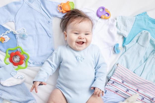 Een baby in blauwe kleren ligt tussen kinderaccessoires en kleding