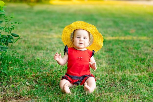 Een baby in een gele hoed en een rode bodysuit op het groene gras in de zomer, ruimte voor tekst