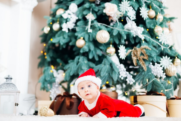 Een baby in een kerstman-pak ligt op een buik bij de kerstboom en cadeautjes