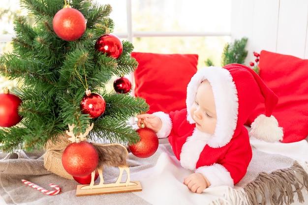 Een baby in een kerstmankostuum onder de kerstboom speelt met rode kerstballen die op het raam van het huis liggen, het concept van het nieuwe jaar