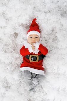 Een baby in een klein kerstmankostuum en hoed ligt op zijn rug in de kunstmatige sneeuw. kerstvakantie. wenskaart