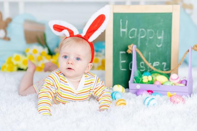 Een baby in een konijnenhoed op een bed met paaseieren en de inscriptie vrolijk pasen