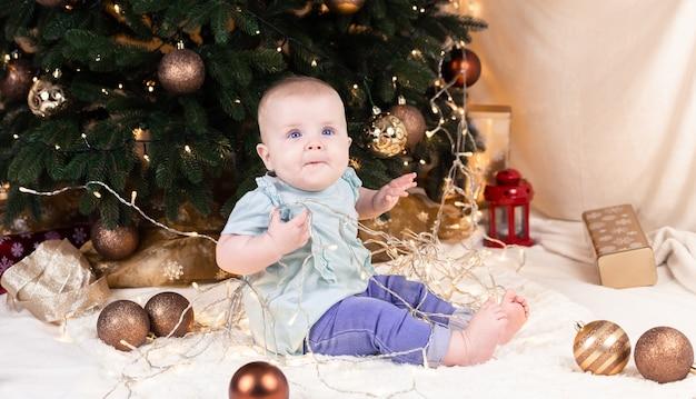 Een baby in spijkerbroek zit bij een kerstboom en speelt met een slinger
