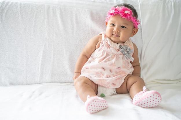 Een baby leert op een wit bed te zitten