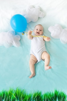 Een baby met een ballon in zijn hand op een blauwe lucht met wolken, het concept van reizen en zomervakantie