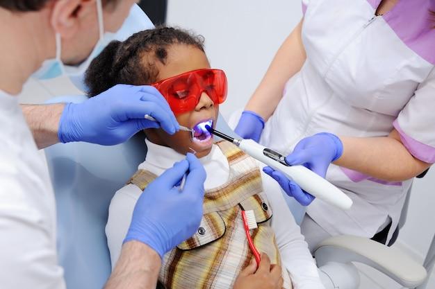 Een baby met een donkere huid in de stoel van de tandarts