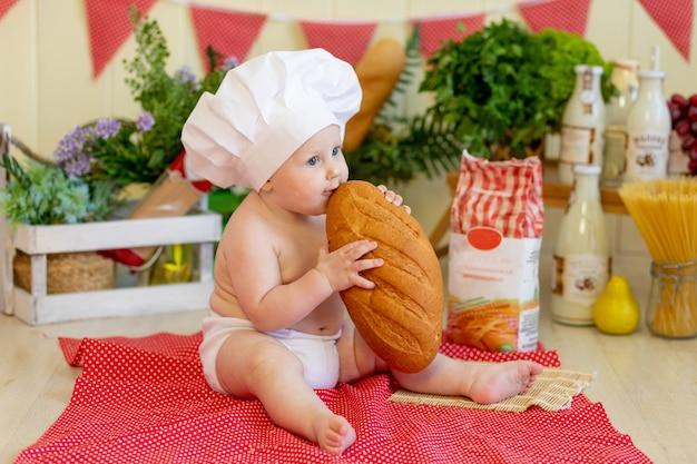 Een baby met een koksmuts leunt achterover in een prachtige fotozone met meel en groenten, een kokskind, een kind met meel en brood maakt eten klaar