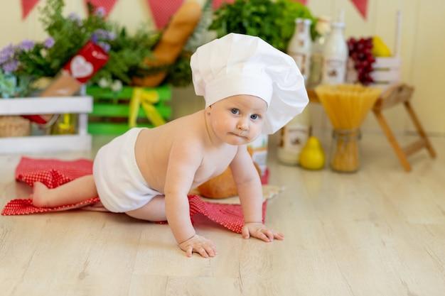 Een baby met een koksmuts zit in een prachtige fotozone met meel en groenten, een babykok, een kind met meel en brood maakt eten klaar