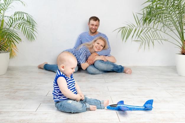 Een baby met een vliegtuig in focus tegen de achtergrond van gelukkige ouders in een nautisch beeld in vesten die plezier hebben, het concept van reizen en recreatie