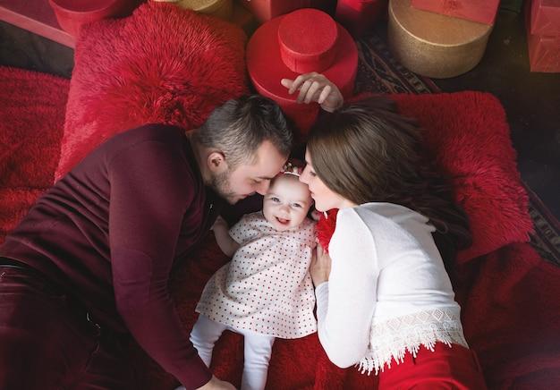 Een baby met ouders in bed wordt omringd door cadeautjes voor de vakantie.