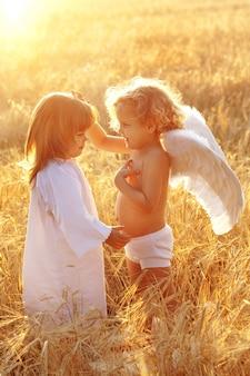Een baby met vleugels raakt een seconde bij de haren in een veld bij zonsondergang