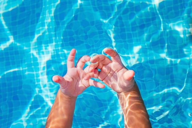 Een baby observeert nieuwsgierig zijn handen ondergedompeld in het water van een zwembad.